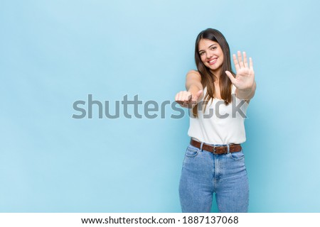 youn pretty woman smiling and looking friendly, showing number six or sixth with hand forward, counting down Foto stock ©