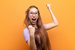 yound blonde woman shouting triumphantly, looking like excited, happy and surprised winner, celebrating