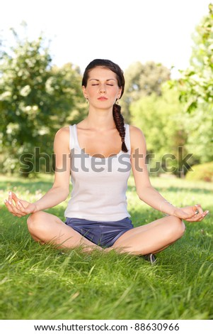 Younf caucasian woman doing youga exercise outside in the park