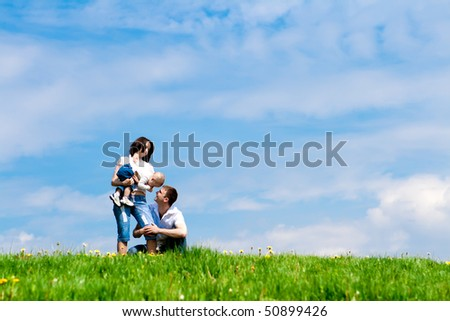 Younf cheerful parents playing with their offspring