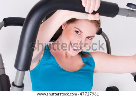Young a beautiful woman is doing some sports in a gym