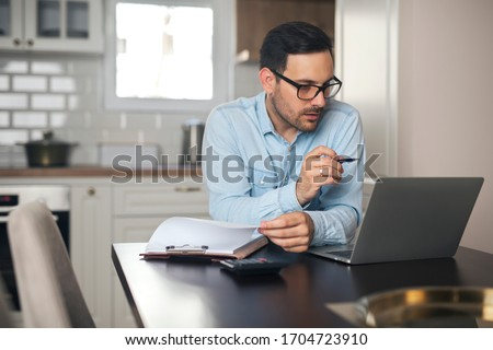 Young accountant work from home looking at a laptop while holding a document and pen in his hands.