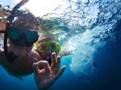 Young active couple snorkeling in a sea and giving ok signal
