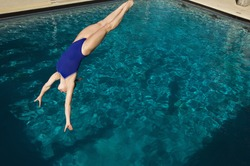 Young active female diver diving into the pool
