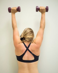 Young active female doing an arm press with weights up in the air at the gym