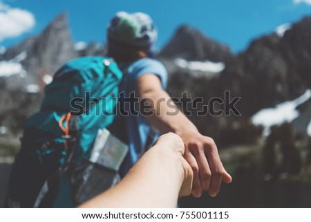 Young active hiking couple with backpacks traveling, woman guiding by the hand into mountain wilderness