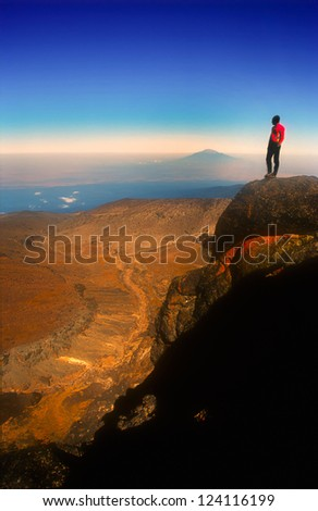 Young active male mountain climber enjoying the view from Mt. Kilimanjaro in Tanzania, Africa. Red Jacket contrast blue sky. Copy space.