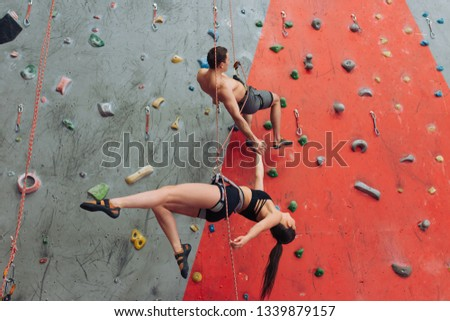 Young active man and woman climbing on artificial rock, man hanging on safety ropes trying to help his girlfriend. dangerous kind of sport #1339879157