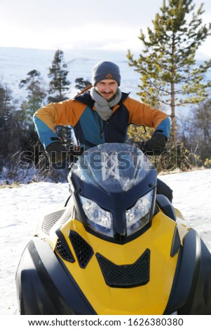 Young active man on a snowmobile in a snowy forest in the mountains in winter. Concept of outdoor activities in a ski resort.