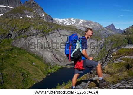 Young active man with backpack hiking on scenic Lofoten islands in Norway on sunny day