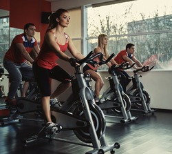 Young active people exercising in spinning class. Group of fit people doing sport in the gym.
