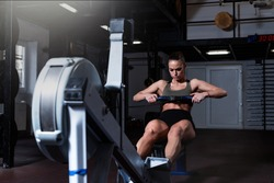 Young active strong fit sweaty powerful attractive muscular woman with big muscles doing hard core row heavy crossfit training workout on indoor rower at the gym real people exercise