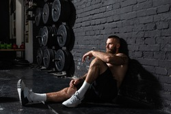 Young active strong sweaty fit muscular man with big muscles sitting on the gym floor and taking a break from hardcore cross workout training real people