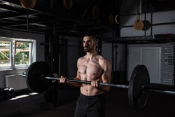 Young active sweaty muscular fit strong man with big muscles doing biceps curly with heavy barbell weight in the gym as hardcore workout cross training real people exercise