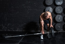 Young active sweaty strong muscular fit man with big muscles putting heavy iron weight plate on the barbell for hardcore gym weightlifting or deadlift cross workout training real people exercising