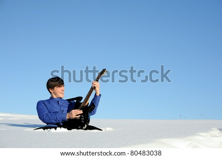 young active teenager with black electric guitar sit in snowdrift