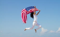 young active woman holding american flag and jumping on beach