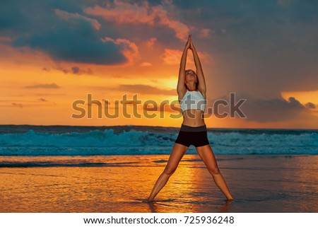 Stock Photo Young active woman in yoga pose on sea beach, stretching to keep fit and health. Healthy lifestyle, outdoor fitness, sports activity on summer family holiday. Sunset background.