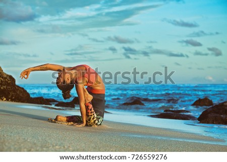 Stock Photo Young active woman sit in yoga pose on sand beach, stretching to keep fit and health.