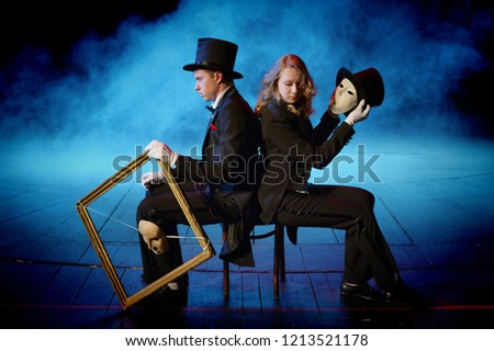 young actors in tuxedos holding theatrical masks #1213521178