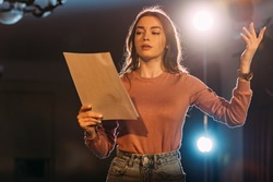 young actress reading scenario on stage in theatre