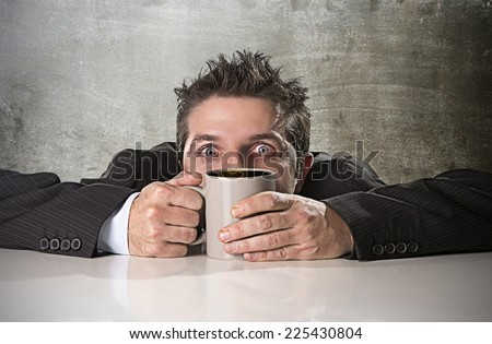 young addict business man in suit holding cup of coffee anxious and crazy in maniac caffeine addiction needing to keep awake leaning on desk on grunge studio background