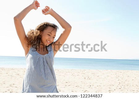 Young adolescent girl being playful, jumping and having fun on a white sand beach on a perfect day with blue sky.