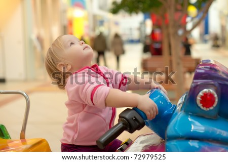 Young adorable baby ride on baby motorcycle in mall. Look up