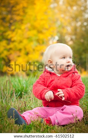 young adorable baby sit on grass under yellow autumn tree