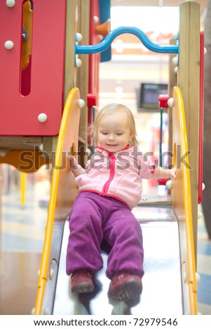 Young adorable baby sliding down baby slide on playground in mall. Start sliding from top
