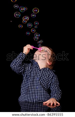 Young adorable 4 year old boy play with bubbles, isolated on black