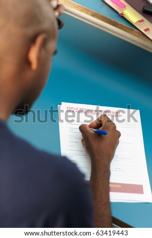 young adult african-american college student filling application form for master degree in library. Vertical shape, rear view, selective focus, head and shoulders