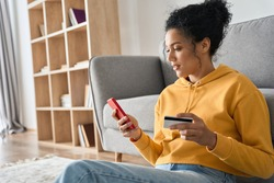 Young adult African American female consumer holding credit card and smartphone sitting on floor at home doing online banking transaction. E commerce virtual shopping, secure mobile banking concept.