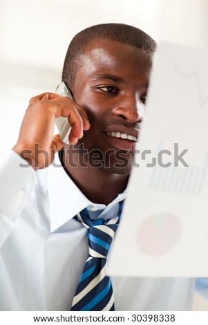young adult afro-american businessman examining charts and talking on the phone