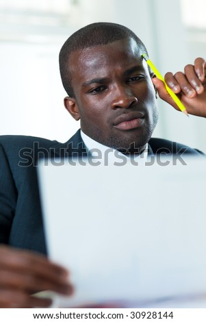 young adult afro-american businessman examining documents indoors