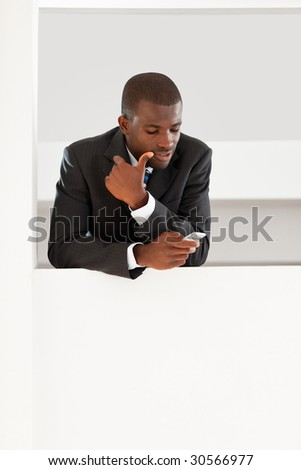 young adult afro-american businessman reading emails on his smartphone indoors. Copy space