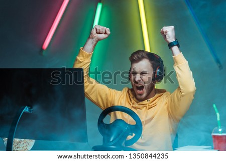 young adult and handsome man in headphones playing video game and showing yes gesture