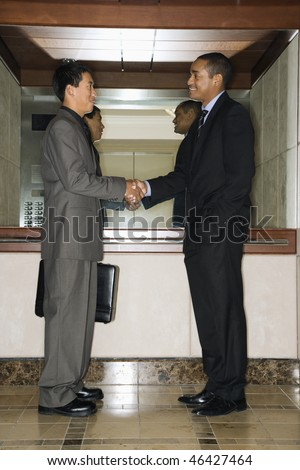 Young adult Asian and African-American businessmen standing in an office lobby shaking hands.
