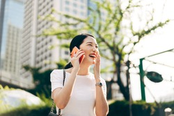 Young adult asian business single woman using mobile phone talking with friend. Happy face and laugh. City lifestyle working people. Backgroud at outdside on day.