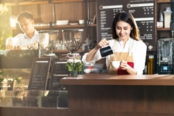 Young adult asian female woman barista pouring fresh milk to prepare latte coffee for customer in cafe bar with her colleague working in background. For small business startup in food industry concept