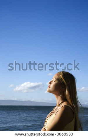 Young adult Asian Filipino female standing on beach in Maui Hawaii.