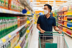 Young adult Asian man wearing a face mask while shopping with cart trolley in grocery supermarket store. He's choosing to buy products in the grocery store during Covid 19 crisis in Thailand