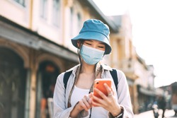 Young adult asian woman backpack traveller wear face mask for corona virus or covid-19. Female using mobile phone applicaiotn. People traveling in city lifestyle at outdoor. Bangkok, Thailand