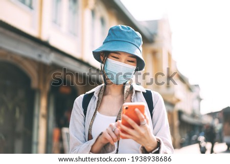 Young adult asian woman backpack traveller wear face mask for corona virus or covid-19. Female using mobile phone applicaiotn. People traveling in city lifestyle at outdoor. Bangkok, Thailand Stock photo ©