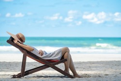 Young adult asian woman tourist in casual wear sleeping nap on beach sun bed on tropical island sand beach in summer day holidays vacation travel trip with blurred blue sea, beach and sky backgrounds.