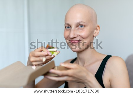 Young adult beautiful caucasian bald shaved hair woman portrait enjoy eating sandwich for lunch at home indoor. Breast cancer survivor person nutrition healthy diet awareness. Chemoterapy alopecia Stock photo ©