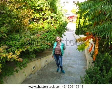 Young adult blonde girl stands on the steps and looks up into the camera. The concept of a tourist walk in the autumn park of Heydar Aliyev in Kiev (Ukraine), a happy and peaceful leisure