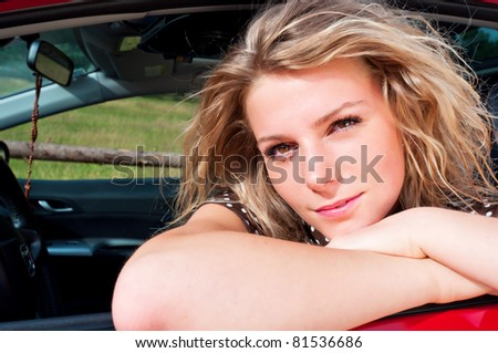 young adult blonde woman leaning on red car