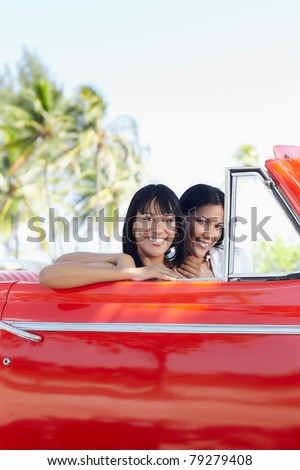 young adult brunette twin women driving convertible red car and looking at camera. Vertical shape, side view, copy space