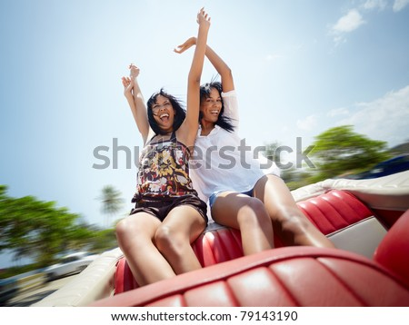 young adult brunette twin women sitting in convertible red car and laughing. Horizontal shape, front view, copy space
